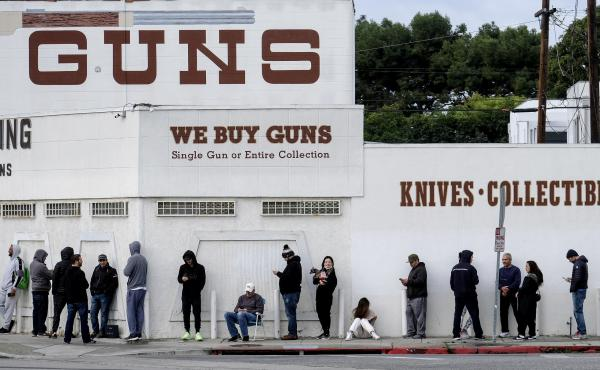People wait in line to enter a gun store in Culver City, Calif., on March 15, 2020.