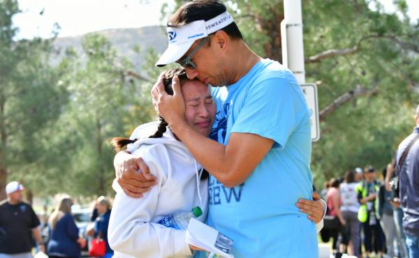 A man embraces his daughter after picking her up at Central Park in Santa Clarita, Calif., after a shooting at Saugus High School on Thursday. At least two people died in the attack, according to local law enforcement.