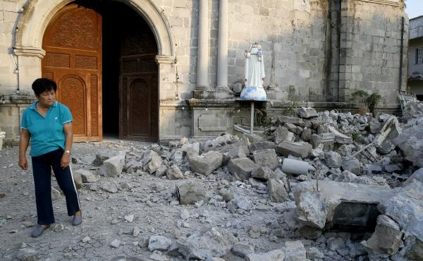 A resident looks at the rubble of St. Catherine church on Tuesday, including the toppled head of a statue, following a 6.1 magnitude earthquake in Pampanga province northwest of Manila the previous day.