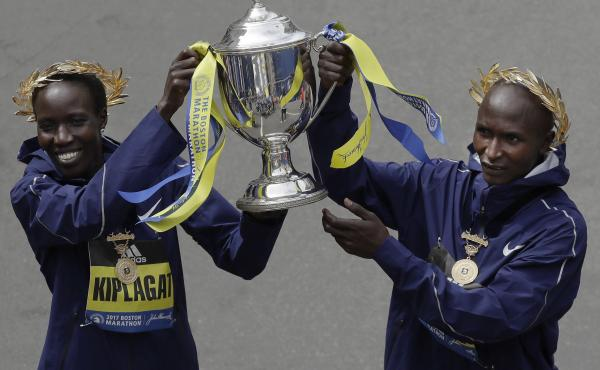 Edna Kiplagat (left) and Geoffrey Kirui, both of Kenya, hold a trophy together after their victories in the 121st Boston Marathon on Monday.