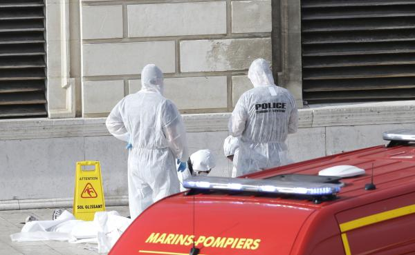 Police officers work outside Marseille's main train station Sunday after a man launched a knife attack, killing two people, before being shot dead.