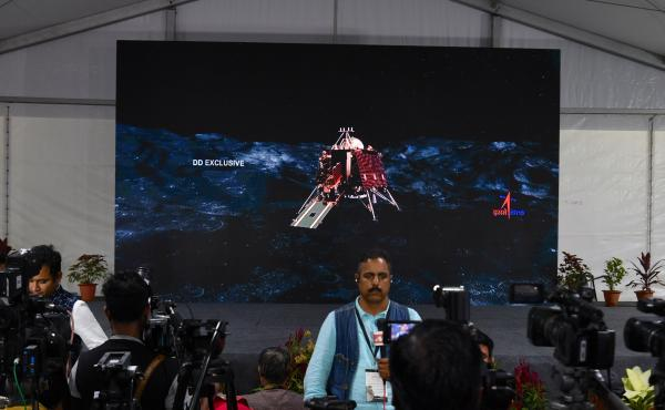 An illustration of the landing craft stands behind members of the media at an Indian Space Research Organisation facility this year in Bangalore, India. Authorities initially chalked up the failed landing in September to a loss of communication with the c