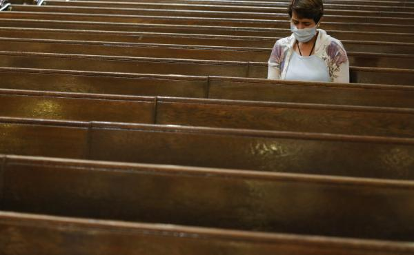 A parishioner sits after Mass last month at a Catholic church in New York City. An overwhelming majority of U.S. adults believe that houses of worship should be subject to the same restrictions on public gatherings that apply to other institutions.