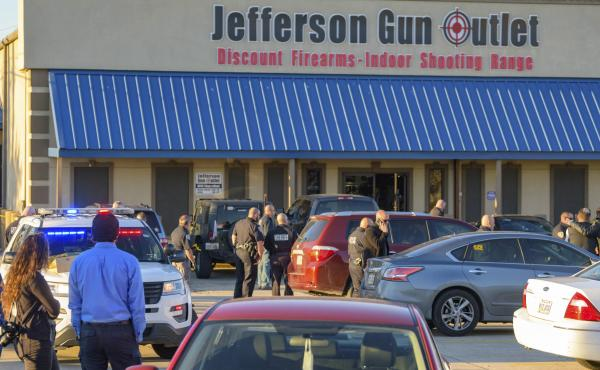 Bystanders gather at the scene of a multiple fatality shooting at the Jefferson Gun Outlet in Metairie, La., Saturday.