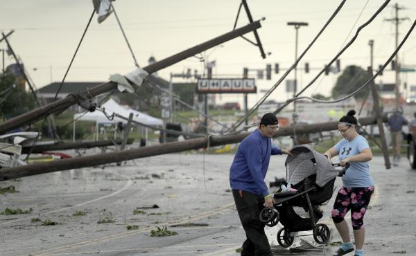 Jessica Rodgers and neighbor Ray Arellana carry a stroller carrying Rodgers' sister Sophia Rodgers over downed power lines as they head to Rodgers' mother's apartment to check on damage on Thursday after a tornado tore though Jefferson City, Mo., late Wed