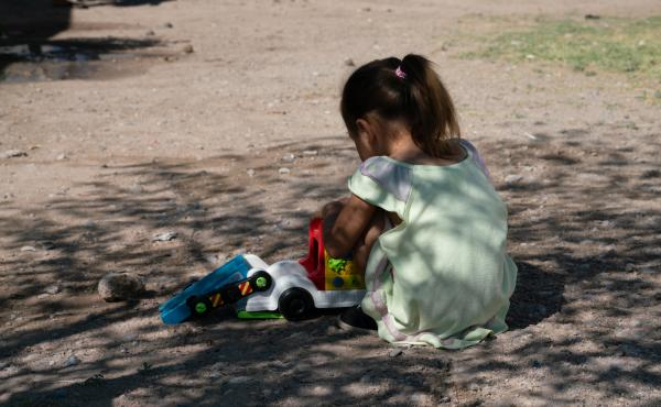 Tania and Joseph's 3-year-old daughter, Sofia, plays with a car in the shade at a shelter in Juárez, Mexico, last week. Sofia has a serious heart condition and had a heart attack.