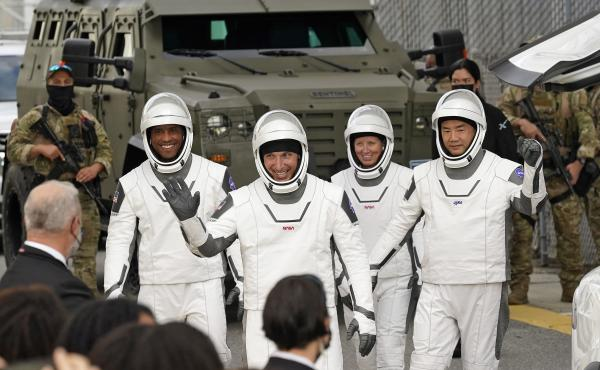 Astronauts (from left) Victor Glover, Michael Hopkins, Shannon Walker and Japan's Soichi Noguchi wave to family and friends as they leave for the launch site on Sunday.