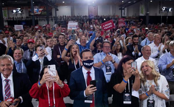 People cheer as President Trump arrives for an indoor campaign rally Sunday night at Xtreme Manufacturing in Henderson, Nev.