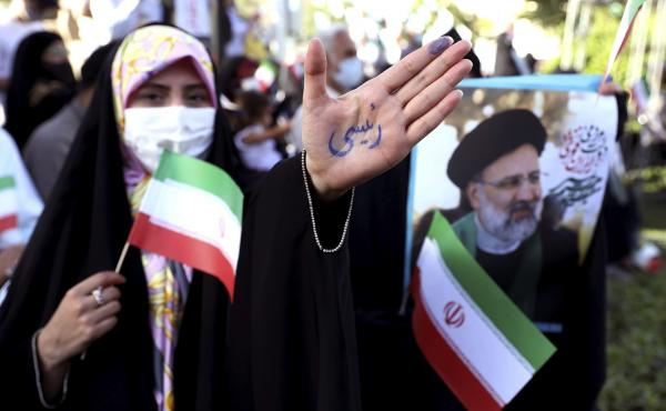 """A supporter of presidential candidate Ebrahim Raisi shows her hand with writing in Persian that reads """"Raisi,"""" during a rally in Tehran, Iran, Wednesday. He is the country's hard-line judiciary chief and is closely aligned with Supreme Leader Ayatollah Al"""