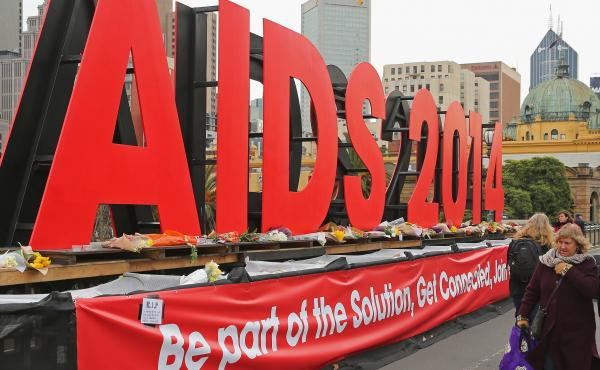 People walk past tributes to the victims of MH17, placed on signage for the 20th International AIDS Conference in Australia in 2014. Several AIDS activists on their way to the conference were killed.