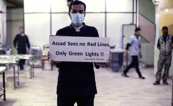A medical worker at a Damascus hospital holds a sign protesting a suspected chemical weapons attack outside the Syrian capital a year ago. The suspected attacks led the U.S. to fire a barrage of missiles at a Syrian air base on April 7, 2017.