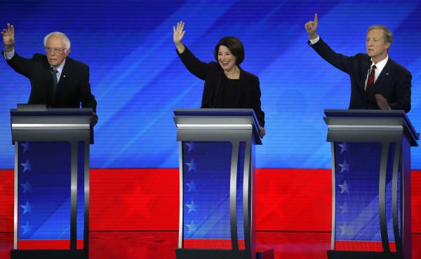 Democratic presidential candidates, Sen. Bernie Sanders (left), Sen. Amy Klobuchar and businessman Tom Steyer raise their hands during a Democratic presidential primary debate on Friday at Saint Anselm College in Manchester, N.H.