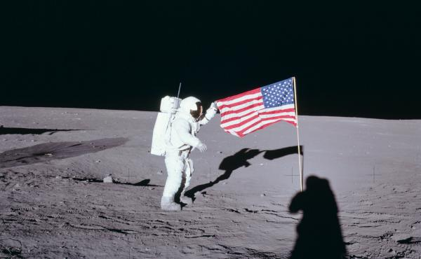 "From NASA: Apollo 12 commander Charles ""Pete"" Conrad unfurls the United States flag on the lunar surface during the first extravehicular activity on Nov. 19, 1969."