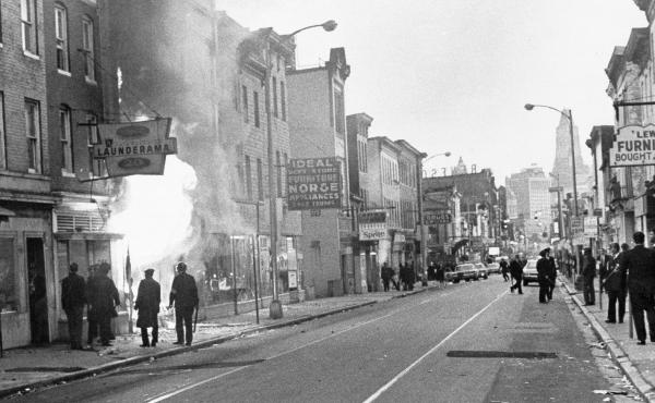 Fire shoots out from a Baltimore store on Gay Street as looting erupted in a five-block business section in Baltimore on April 6, 1968. Police sealed off the area.