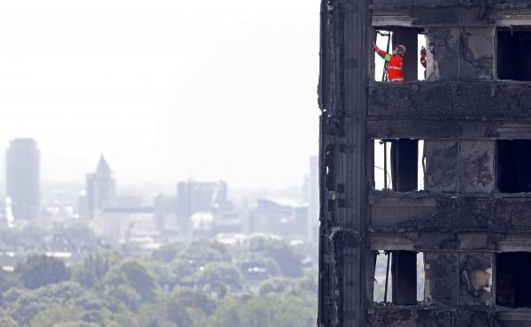 """Emergency service workers probe the remains of Grenfell Tower in London on Saturday. City police have announced 58 people remain missing and """"we assume likely to have died."""""""
