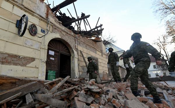 Croatian soldiers walk next to damaged buildings Tuesday in Petrinja, some 30 miles from the capital, Zagreb, after the town was hit by a 6.4 magnitude earthquake.