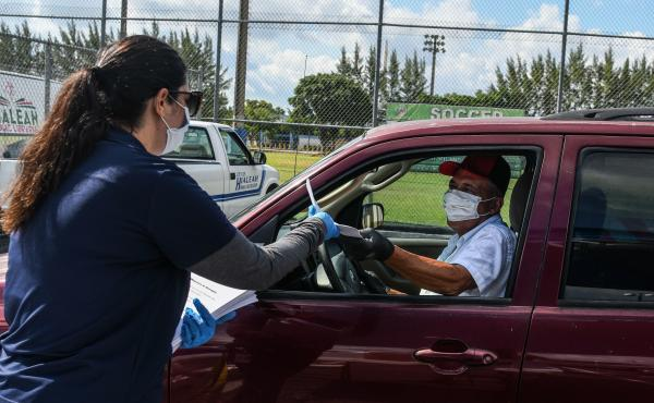 A man collects unemployment forms at a drive-through collection point outside of a library in Hialeah, Fla., on Wednesday.