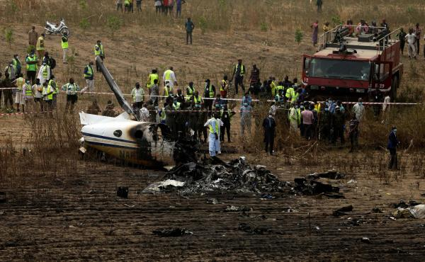 Emergency personnel work at the scene a Nigerian military aircraft crash near Abuja, Nigeria, on Sunday. All seven people on board were killed.