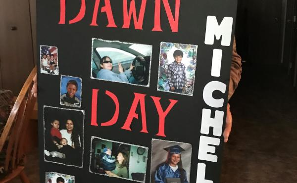 Gregory Day holds a placard covered in photos of his deceased daughter, Dawn. It's the one he carried in a Missing and Murdered Indigenous Women's march last spring.