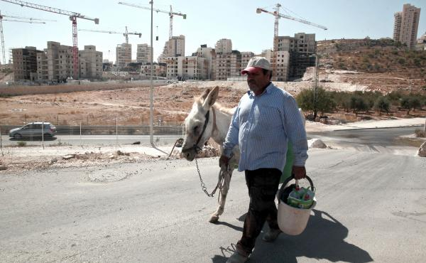 A Palestinian man walks near a construction site for new Israeli housing in the East Jerusalem neighborhood of Har Homa in September. The Palestinians claim East Jerusalem as a capital of a future state and object to Israeli building in the eastern part o