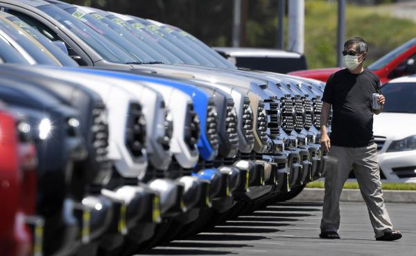 A customer looks at trucks Friday at a Toyota dealership in El Monte, Calif. Car sales have been recovering for several weeks despite the continuing coronavirus outbreak.