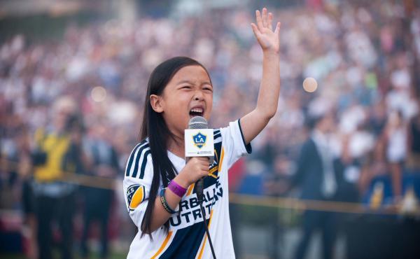 Malea Emma Tjandrawidjaja, 7, sings the national anthem on Sunday night at a LA Galaxy soccer game.