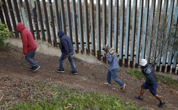 Central American migrants walk along the U.S. border fence looking for places to cross, in Tijuana, Mexico.