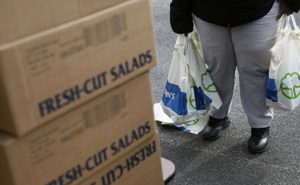 An FDA contract worker collects food and supplies from a food pantry in Baltimore. In the face of a Trump administration proposal that could cause 3 million people to lose federal food assistance, mayors from 70 cities are pushing back.