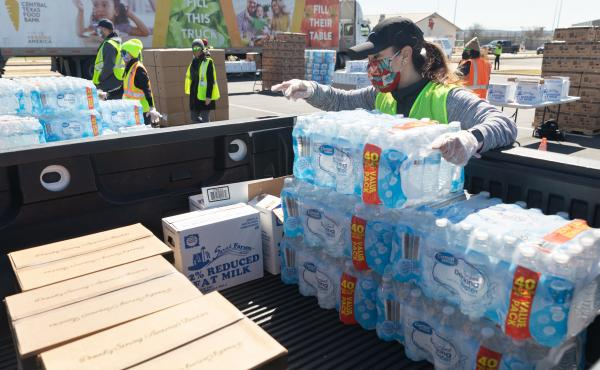 One week after winter storms triggered boil-water notices in Texas, more than 8.7 million people are still affected. Here, a volunteer loads food and bottled water at a mass distribution site in Del Valle, Texas.