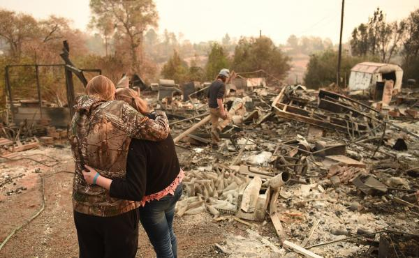 Kimberly Spainhower hugs her daughter Chloe, 13, while her husband Ryan Spainhower searches through the ashes of their burned home in Paradise, Calif., last week.