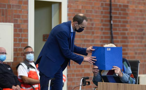 Lawyer Stefan Waterkamp covers the face of accused Josef S. at the court room in Brandenburg, Germany, on Oct. 7, 2021. The 100-year-old man is charged as an accessory to murder on allegations that he served as a guard at the Nazis' Sachsenhausen concentr