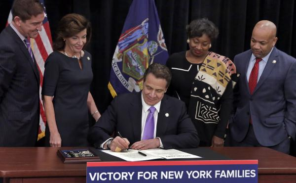 New York Gov. Andrew Cuomo signed a law Monday that will establish a paid-family-leave policy and gradually raise New York's minimum wage, at the Javits Convention Center in New York City.