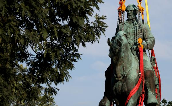 """Workers remove a statue of Confederate Gen. Robert E. Lee from Market Street Park in Charlottesville, Va., in July. Initial plans to remove the statue four years ago sparked the infamous """"Unite the Right"""" rally at which 32-year-old Heather Heyer was kille"""