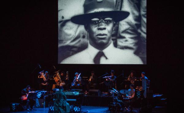 A photograph of jazz pianist James Reese Europe projected above the musicians performing Jason Moran's James Reese Europe and the Absence of Ruin.