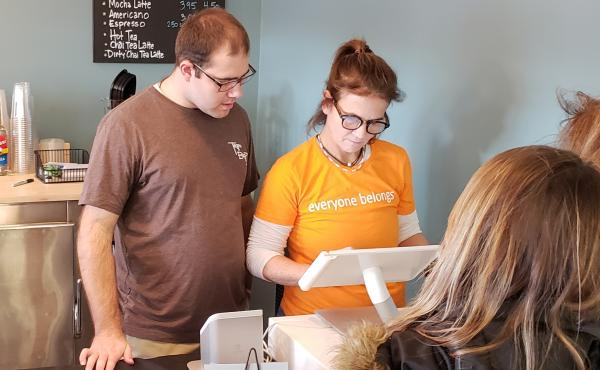 Kim Morrison, (right) co-owner of Beanz & Co. Cafe in Avon, Conn., with her employee, Nick Sinacori, as they serve customers during their opening week.