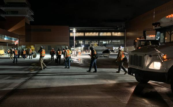 RK workers depart a bus on their way to the job site at a new airport under construction in Salt Lake City.