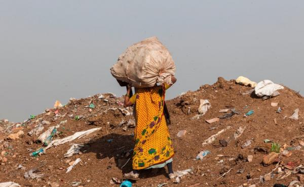 A trash picker carries a sack of recyclable materials she collected at the Ghazipur landfill in the east of New Delhi.