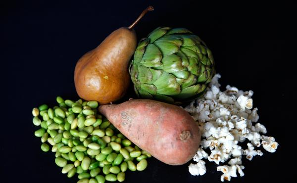These fiber-rich foods altogether offer about 28.5 grams, or a woman's daily recommended intake. Clockwise from top left: one pear, 6 grams of fiber; medium artichoke, 7 grams; 1 ounce of popcorn, 3.5 grams; 1 medium sweet potato, 4 grams; 1 cup edamame,