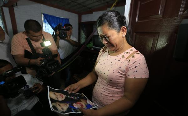Rosa Ramírez cries as she looks at photos of her son Óscar Alberto Martínez Ramírez, 25, and granddaughter Valeria, nearly 2, while speaking to journalists at her home in San Martín, El Salvador, on Tuesday. The drowned bodies of her son and granddau
