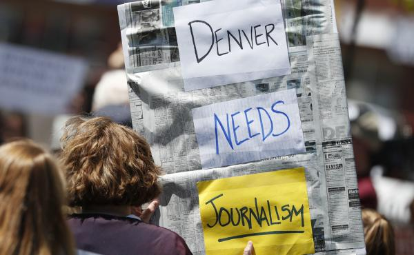 An Denver Post employee holds up a sign during a rally against the paper's ownership group, Alden Global Capital, on May 8 outside the paper's office. A series of layoffs have slashed the paper's newsroom staff.