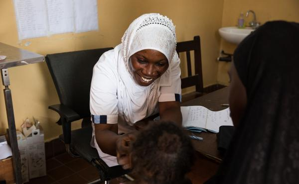 Nabia Drammeh, 27, a nurse, talks with Maram Ceesay, and her granddaughter, Awa at the Brufut Minor Health Center outside of Banjul, the Gambia. Awa's mother passed away during childbirth leaving her Maram to look after her. The 2-year-old is being treate