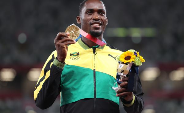 Gold medalist Hansle Parchment of Jamaica holds up his medal on the podium during the medal ceremony for the men's 110-meter hurdles on Aug. 5.