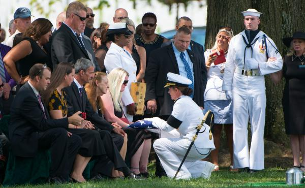 Erin Rehm receives the American flag from Vice Adm. Jan Tighe during the graveside service for her husband, U.S. Navy Fire Controlman 1st Class Gary Rehm Jr. at Arlington National Cemetery on Aug. 16. He was one of seven sailors killed on June 17 when the