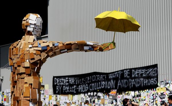 """A scrap-wood sculpture of a man holding an umbrella is the contemporary equivalent of the """"Goddess of Democracy."""" The umbrella became a symbol of the democracy demonstrations after protesters used them to block police pepper spray and tear gas attacks lat"""