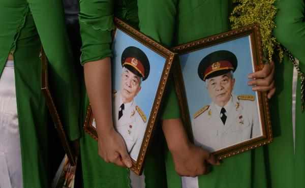 A photo taken in 2013 shows women in traditional dress holding framed portraits of the late Gen. Vo Nguyen Giap as they line up to pay final respects to him at his residence in Hanoi.