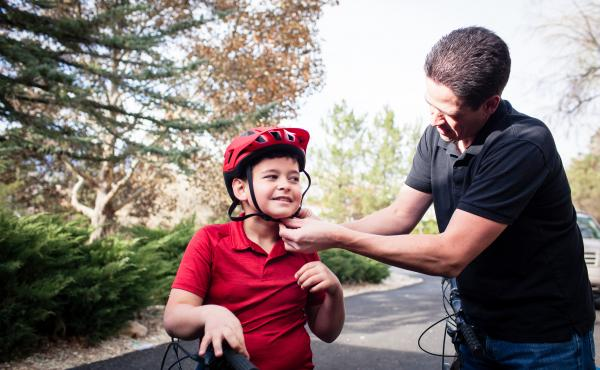 Adam Woodrum and his son, Robert, get ready for a bike ride near their home in Carson City, Nev., this month. During the summer, Robert had a bike accident that resulted in a hefty bill from the family's insurer.
