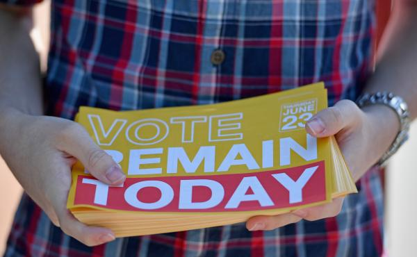 """A young man hands out """"Remain"""" leaflets outside the polling station at Notre Dame Primary School on Thursday in Glasgow, Scotland. As a nation, Scotland voted to remain in the EU; but as a whole, the United Kingdom opted to leave."""