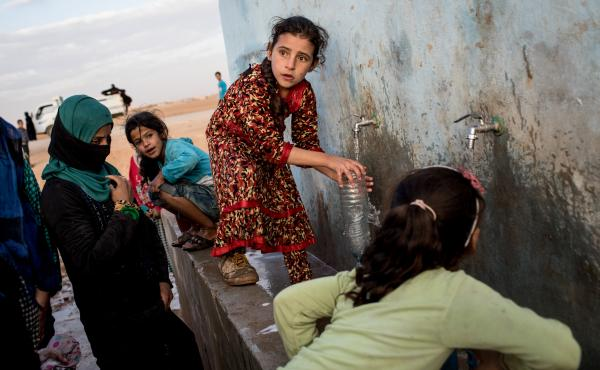 Access to water is increasingly entangled with conflict situations. (Above) A young girl fills a bottle at a pump station at a camp for internally displaced people in Ain Issa, Syria.