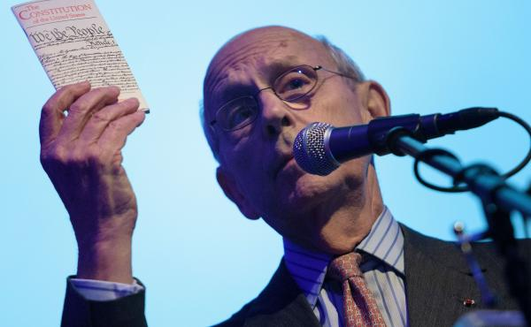 U.S. Supreme Court Justice Stephen Breyer holds up the U.S. Constitution at a talk in 2016.