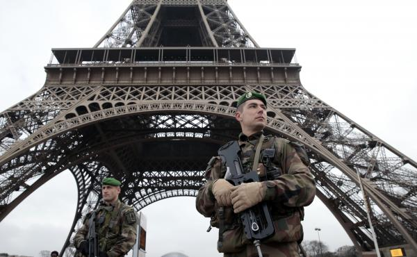 French soldiers patrol in front of the Eiffel Tower on Wednesday, after heavily armed gunmen stormed the offices of Charlie Hebdo and killed at least 12 people — the deadliest attack in France in four decades.